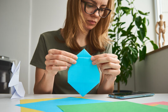 DIY concept. Woman make origami easter rabbit from color paper. Origami lessons