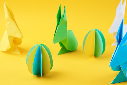 Paper origami Esater rabbits and colored eggs on yellow background. Easter celebration concept