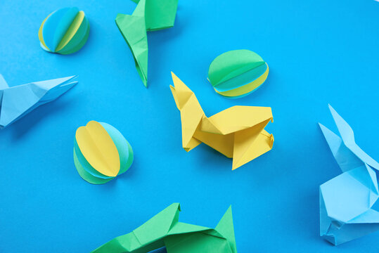 Paper origami Esater rabbits and colored eggs on blue background. Easter celebration concept
