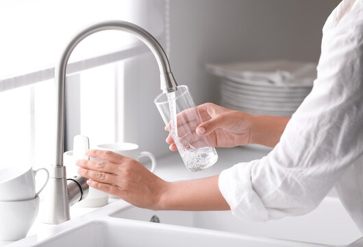 Woman pouring water into glass in kitchen, closeup