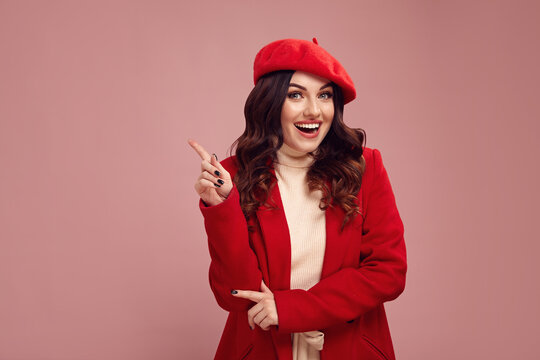 Funny young woman in a red coat and beret points her finger up on a pink background