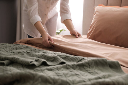 Woman making bed with stylish linens in room, closeup