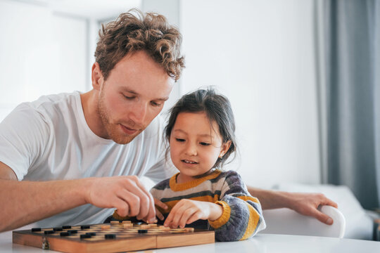 Single father with his daughter is at home together at daytime. Playing checkers