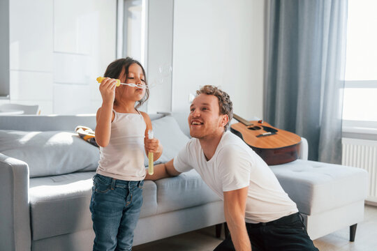 Single father with his daughter is at home together at daytime. Playing with bubbles