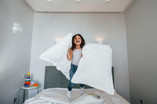 Happy young little girl have fun by jumping on the bed at home