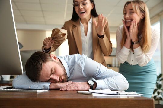 Young women popping paper bag their behind sleeping colleague in office. Funny joke