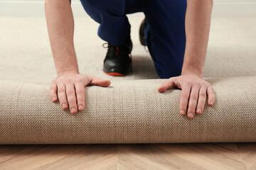 Obraz Worker rolling out new carpet flooring indoors, closeup - fototapety do salonu