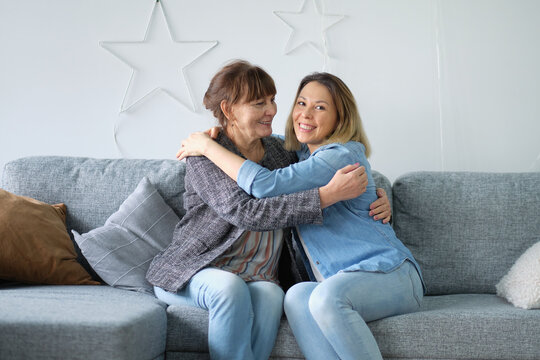 Head shot of beautiful adult daughter hug older mother at home, happy female two age generation family love