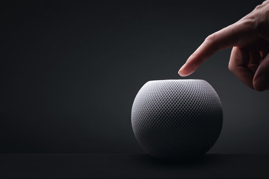 Apple HomePod mini with a hand on dark background