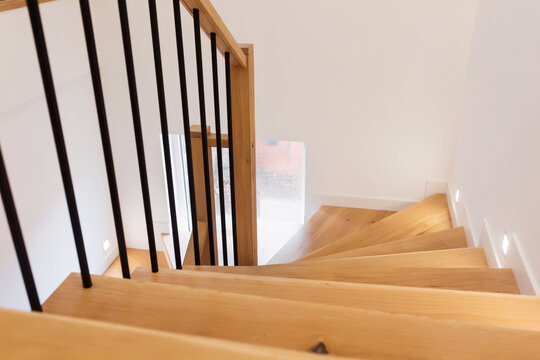 Wood staircase inside contemporary white modern house.