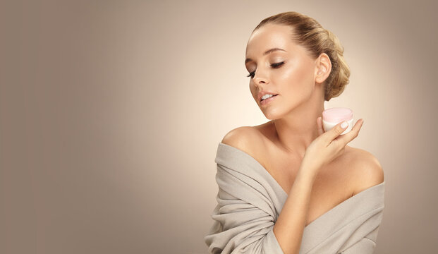 Beautiful caucasian blonde woman shows face cream on palm of hand over beige isolated with free copy space.