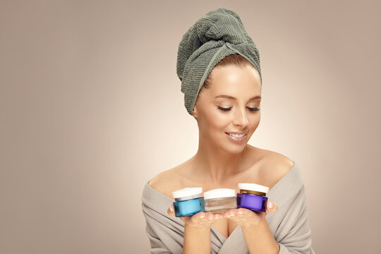 Beauty portrait, smiling woman holds various skin creams on beige isolated.