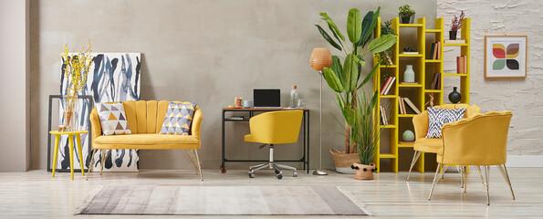 Fototapeta Decorative grey stone wall living room, home interior concept with yellow sofa chair and bookshelf, big green vase of plant carpet. obraz