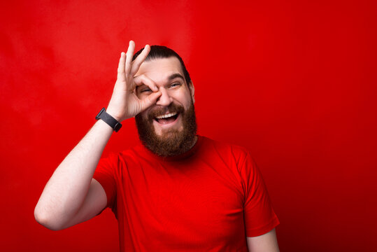 Photo of amazed bearded man showing ok gesture over red background