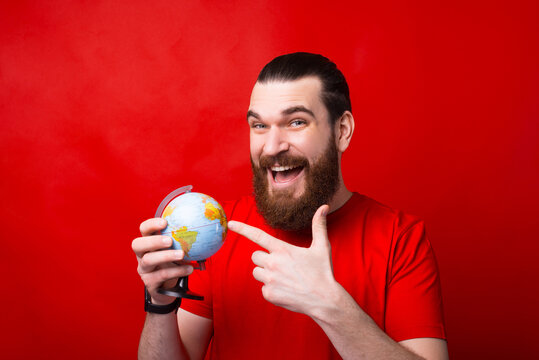 Amazed young bearded man pointing at globe, next destination