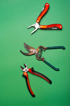 Top view photo of some gardening tools over green background