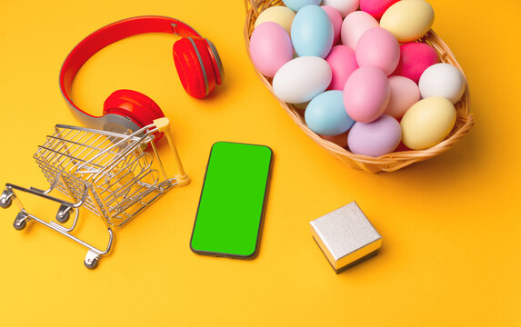 Top view of easter eggs smartphone with green screen and shopping basket