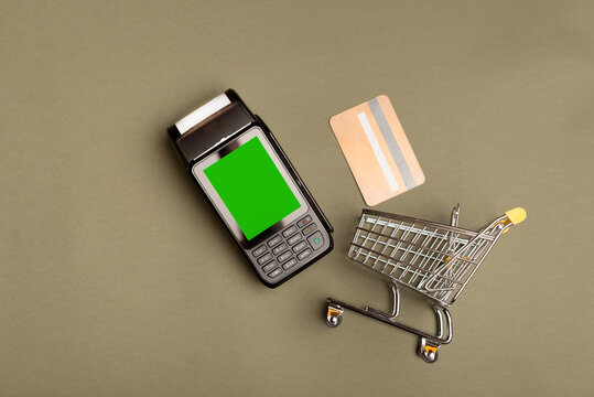 Top view photo of credit card small shopping trolley and pos terminal