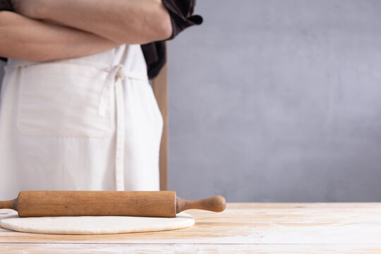 Baker man kneading or making dough and rolling pin for homemade bread cooking. Bakery concept