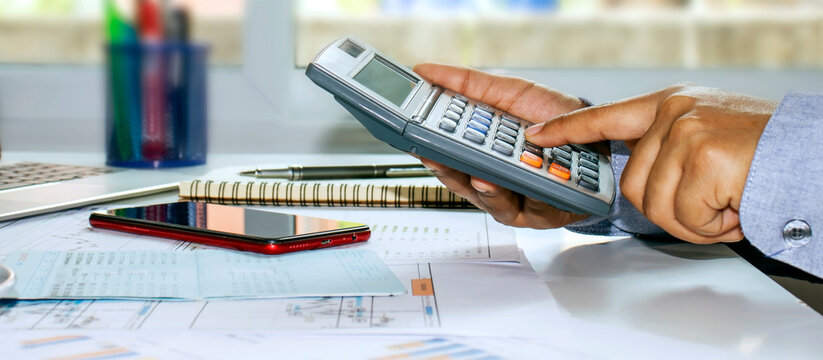 A panoramic picture of a business man pressing a calculator and taking notes of accounting reports, concepts of costing and saving money.