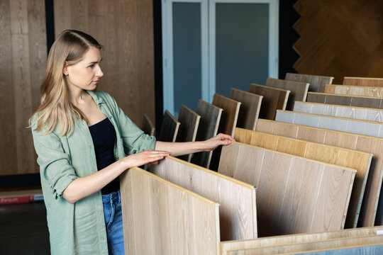 woman choosing laminate floor design from samples in flooring store