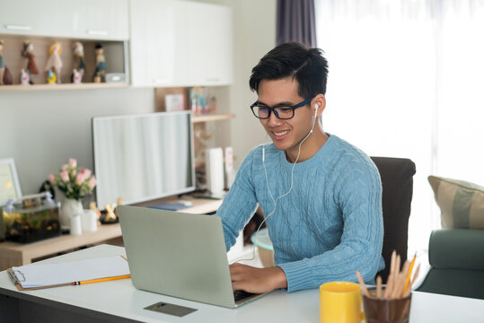 Young Asian man wearing headphones is using a laptop at home.