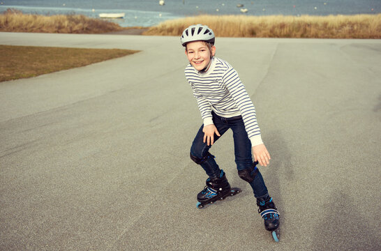 Happy teenager boy in helmet, inline skates and safety equipment is happy learning skating sunny day