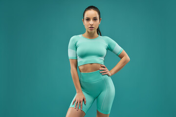Attractive young woman in sportswear standing against green background
