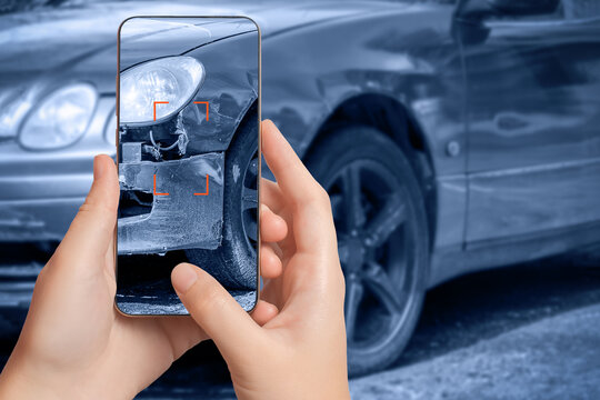 A girl takes pictures on a smartphone of car damage at the scene of an accident for insurance compensation. Selective focus.