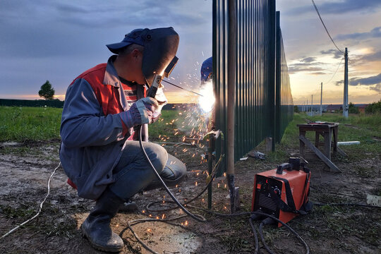 welding of a metal profile to a fence, process of welding close-up, the worker in a protective helmet against sparks.