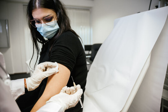 Nurse holds syringe in hand and cleans arm to woman - Doctor in hospital gives vaccine against Coronavirus Covid-19 patient - Medical practitioner vaccinates young woman in clinic office - Copy space