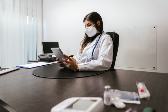 Female doctor at her desk in the hospital while analyzes a patient's medical record and analysis before the meeting, wearing protective face mask during the Coronavirus Covid-19 pandemic - Copy space