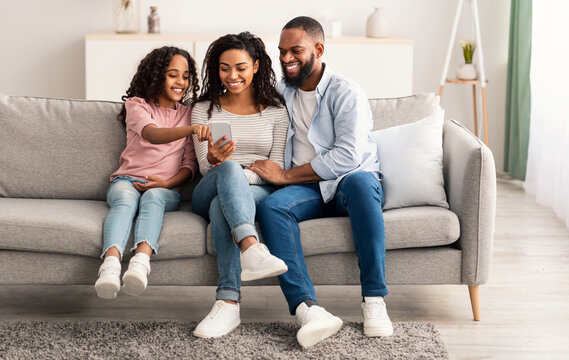 Happy african american family holding and using smartphone