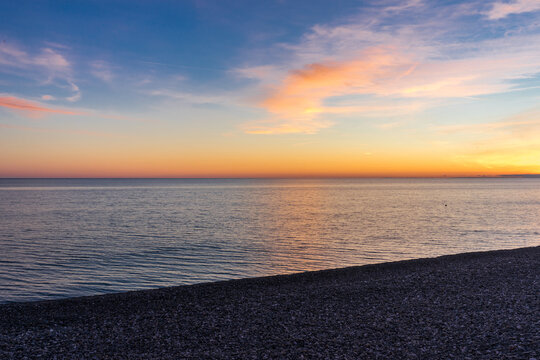 Pebble beach and beautiful sunset on the Black Sea in Sochi, in Adler in the spring.