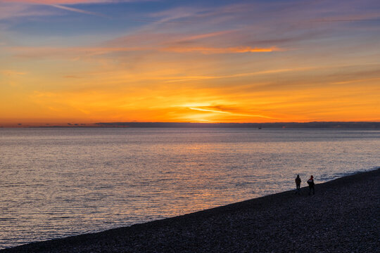 Beautiful sunset on the beach in Sochi, in Adler in spring. Silhouettes of people on the beach