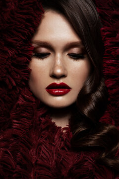 A beautiful girl with evening make-up, a curls wave and red lips. Beauty face.