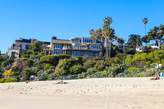 a gorgeous lush green hillside at the beach with beachfront homes and blue sky at West Street Beach in Laguna Beach California