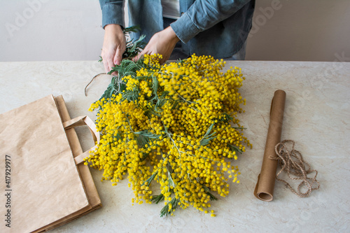 Woman make a bouquet of yellow spring flowers. Mother's day, Valentine's day, international women's day, March 8