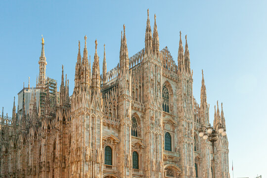 Famous church Milan Cathedral Duomo di Milano with Gothic spires and white marble statues. Top tourist attraction on piazza in Milan Lombardia Italy Wide angle view of old Gothic architecture and art