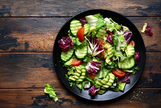 Fresh delicious vegetable salad with avocado, tomato, cucumber. Top view with copy space.