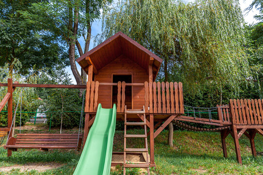 Empty modern wooden children playground set on green yard in public park in summer day. Funny toy land for kids. Urban exercise activities for child outdoors. Neighborhood childhood concept