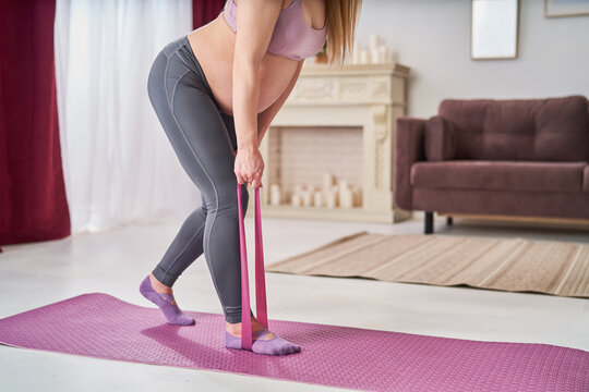 happy attractive pregnant woman in sports clothes does exercises with an elastic sports elastic band on mat, at home. health during pregnancy. sports at home. Motherhood, active pregnancy.