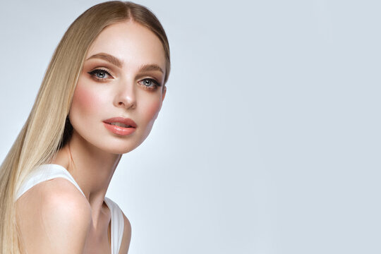 Beautiful blond girl with a perfectly smooth hair, and classic make-up. Beauty face and hair.