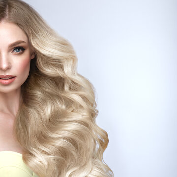 Beautiful blond girl with a perfectly curls hair, and classic make-up. Beauty face and hair.