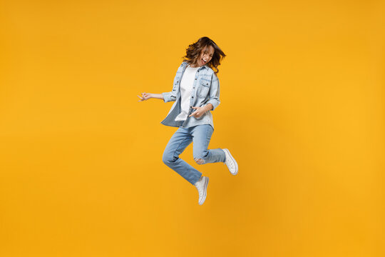 Full length of young overjoyed excited fun expressive student happy woman 20s wearing casual denim shirt white t-shirt playing guitar jump high isolated on yellow color background studio portrait