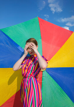 Woman shielding eyes while standing against colorful beach umbrella