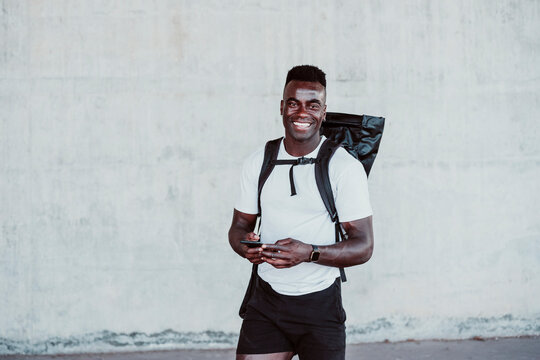 Smiling male athlete holding smart phone standing against wall