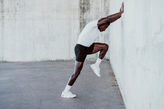 Sportsman doing stretching workout while leaning on white wall