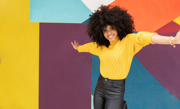 Carefree woman dancing with arms outstretched against multi colored wall