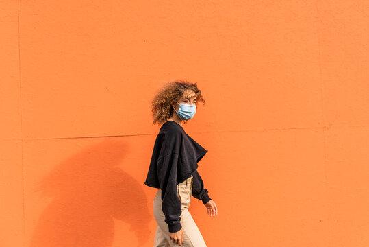 Woman wearing face mask walking against orange wall